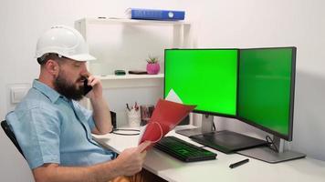 un bel opérateur masculin contrôle l'installation, utilise un ordinateur avec plusieurs écrans verts à clé chroma. en arrière-plan, une installation de production d'électronique automatisée sombre photo