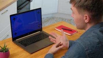 l'homme a laissé la vue d'un homme intelligent parlant avec un collègue tout en faisant un appel vidéo sur un ordinateur portable avec un écran chromakey tout en travaillant à la maison. photo