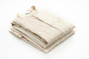 Chemises beiges pliées isolé sur fond blanc photo