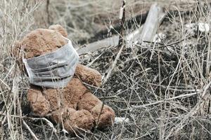ours en peluche dans un masque médical assis dans les ordures photo