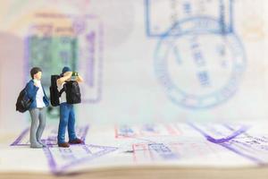 Couple de personnes miniatures debout sur un passeport avec tampon d'immigration photo