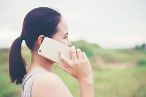 belle jeune femme utilisant un smartphone et souriant dans le parc. photo