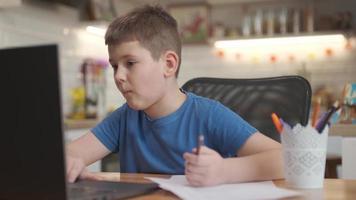 concept de leçon d'enseignement à distance en ligne. enfant garçon enfant écolier avec enseignant utilisant un ordinateur portable tablette pour écrire des devoirs scolaires, étudier à la maison. photo