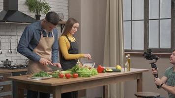 vidéaste filmant une scène de cuisine. couple amoureux préparant un repas sain à la cuisine à la maison photo