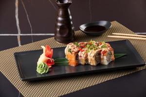 rouleaux de sushi d'anguille sur fond noir. service de restaurant photo