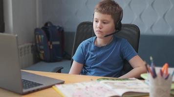 un petit garçon intelligent utilise l'ordinateur pour discuter en vidéo avec son professeur. e-éducation enseignement à distance, enseignement à domicile, covid. apprentissage de l'éducation en ligne, un étudiant adolescent porte un casque photo
