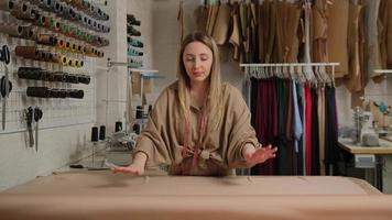 Close up of female tailleur déroulant un gros rouleau de tissu sur table au design studio photo