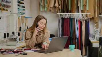 un entrepreneur sur mesure à succès parle sur un téléphone portable et utilise un ordinateur portable. la femme est occupée à commander du tissu auprès d'un fournisseur de textile. concept de démarrage de conception de vêtements. photo
