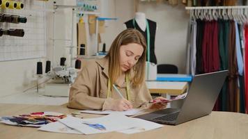 gros plan sur une femme designer utilise son ordinateur portable travaillant au studio de design. le tailleur regarde des échantillons de tissu et prend des notes photo