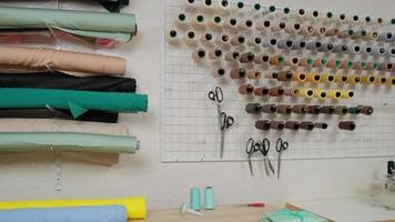 atelier de tailleur studio, confection de vêtements sur commande. intérieur du petit studio de mode. vue des rouleaux de tissu, des bobines de fil et des motifs photo