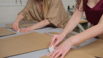 gros plan de créateurs de mode motif de farinage sur tissu à l'atelier. deux tailleurs femail travaillant sur le lieu de travail. concept de mode et de couture. petite entreprise photo