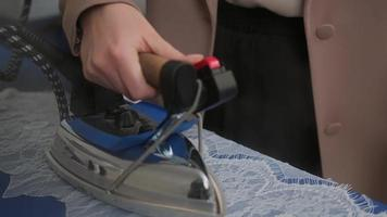 Siview incliner vers le bas plan moyen d'une dentelle à la vapeur sur mesure le préparer pour la couture debout à la planche à repasser en atelier photo