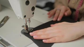 couture sur machine à coudre. tailleur coud sur machine à coudre. gros plan de la main de la femme et du processus de couture. photo