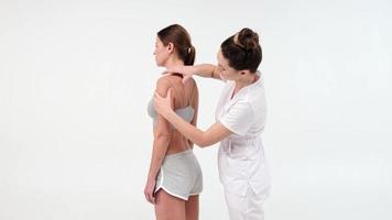 physiothérapeute ou chiropraticien massant l'épaule d'une patiente. vue du masseur effectuant un massage des tissus profonds. séquences d'archives 4k. gros plan vidéo. photo