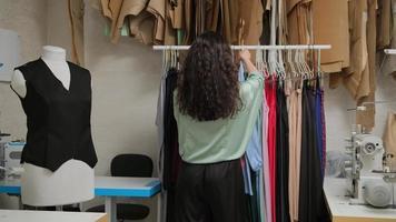 atelier de tailleur. suspendre des vêtements sur un cintre. créateur de vêtements à la recherche d'un cintre au studio de l'atelier photo