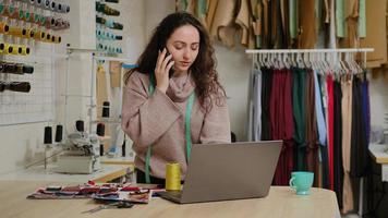 un entrepreneur sur mesure à succès parle sur un téléphone portable et utilise un ordinateur portable. la femme est occupée à commander du tissu auprès d'un fournisseur de textile ou à passer la commande du client. concept de démarrage de conception de vêtements. photo