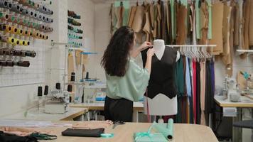 la couturière mesure des vêtements sur un mannequin de couture avec un ruban à mesurer. la femme est concentrée et réfléchie. Le studio est léger, moderne, avec de nombreux outils et articles de couture. photo
