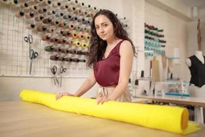 tailleur féminin cuaucasien prenant un rouleau de tissu pour la coupe de motifs. créateur de mode professionnel mesurant le matériau textile. industrie du vêtement, processus de confection, concept d'atelier de confection de vêtements photo