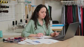 créateur de mode compétent créant de nouveaux croquis sur ordinateur portable. tailleur femail assis à l'atelier studio atelier. photo