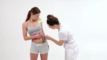 rubans adhésifs de physiothérapeute. ruban kinesio sur le ventre de la fille. jeune fille caucasienne avec un ruban thérapeutique élastique de kinésiologie sur son ventre. photo