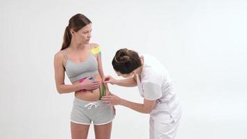 ruban kinesio sur le ventre de la fille. jeune fille caucasienne avec un ruban thérapeutique élastique de kinésiologie sur son ventre. femme appliquant du ruban adhésif spécial sur l'abdomen de la femme photo