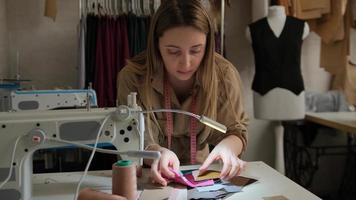 une couturière examine des échantillons de tissu à côté d'une machine à coudre photo