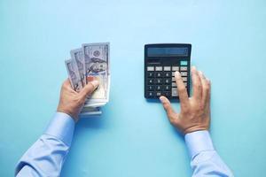 main de l'homme à l'aide d'une calculatrice et tenant de l'argent en dollars américains photo