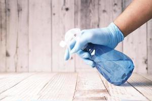 main dans des gants en caoutchouc bleu tenant une table de nettoyage de flacon pulvérisateur photo