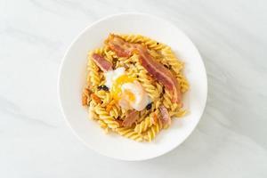 Pâtes fusilli carbonara bacon épicé - style cuisine italienne photo