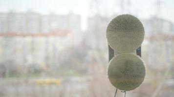 assistant de robot domestique nettoyant la vitre. fenêtre de nettoyage d'aspirateur dans un bâtiment élevé en plein air. photo