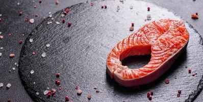 steak de poisson rouge de truite crue servi avec des herbes et du citron photo