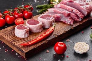 morceaux de porc frais prêts à cuire sur fond sombre photo