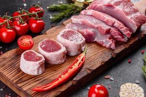 morceaux de porc frais prêts à cuire sur fond sombre dans la cuisine photo