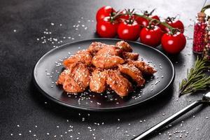 filet de poulet aux graines de sésame, sauce teriyaki sur plaque de pierre noire photo