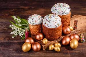 oeufs de pâques or et bronze et gâteau de pâques sur fond sombre photo