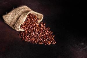 grains de café torréfié frais close-up sur un fond sombre photo