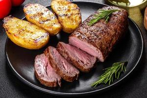 steak de faux-filet avec pommes de terre, oignons et tomates cerises photo