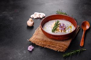 délicieuse belle soupe aux champignons dans une assiette brune avec une cuillère en bois photo