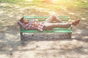 jeune homme hipster allongé sur un banc de parc verdoyant, à l'écart. photo