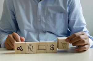 main d'homme tenant le cube sur l'icône de marketing d'achats en ligne de table photo