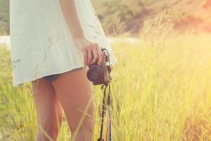 Vintage femme photographe debout main tenant un appareil photo rétro