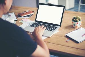 les mains de l'homme tapant travaillant avec un ordinateur portable sur un bureau en bois photo