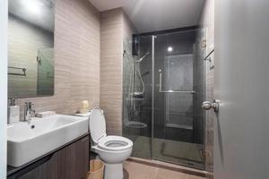 salle de bain moderne et bois blanc avec cabine de douche en verre dans l'appartement photo