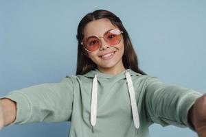 adolescente souriante et positive tenant un appareil photo