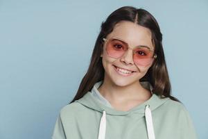 Une adolescente mignonne et attirante à lunettes de soleil regarde la caméra photo
