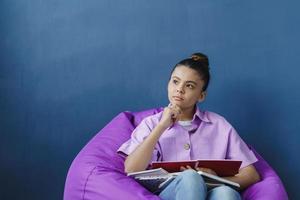 adolescente concentrée assise dans un pouf, étudiant photo