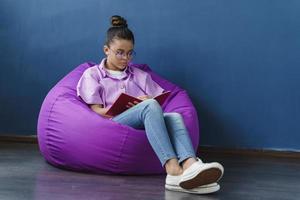 adolescente concentrée et mignonne assise dans un pouf violet, étudiant photo