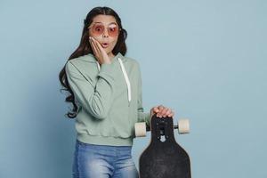 adolescente surprise dans des lunettes de soleil tenant une planche à roulettes photo