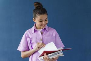 jolie adolescente regarde dans ses cahiers sur fond bleu photo