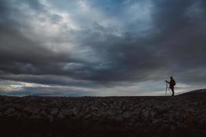 silhouette d'un photographe ou d'un voyageur avec trépied debout sur pierre photo